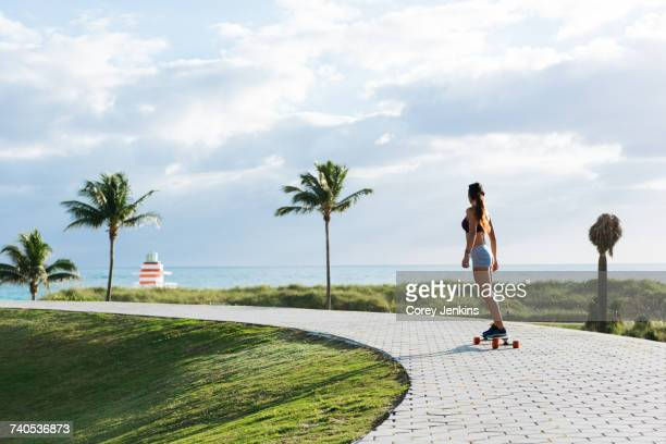 Young woman skateboarding in park, rear view, South Point Park, Miami Beach, Florida, USA