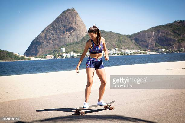 Young woman skateboarding on pavement