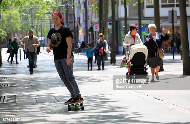 a young woman skateboarding on pedestrian street - vitoria spain stock pictures, royalty-free photos & images