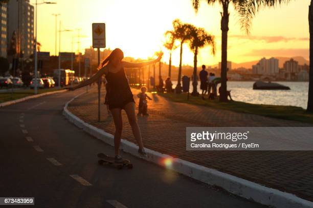 Young Woman Skateboarding On Street During Sunset