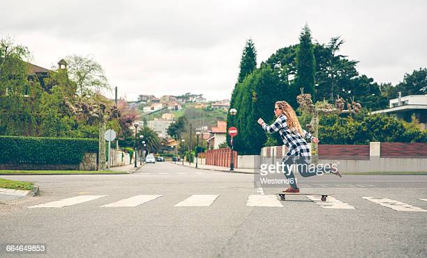 young woman skateboarding on the street - zebra crossing stock pictures, royalty-free photos & images
