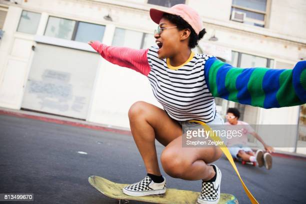 young woman skateboarding - ungestellt stock-fotos und bilder
