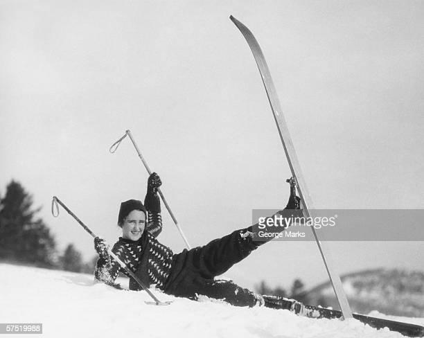 Young woman skier fallen in snow, (B&W)