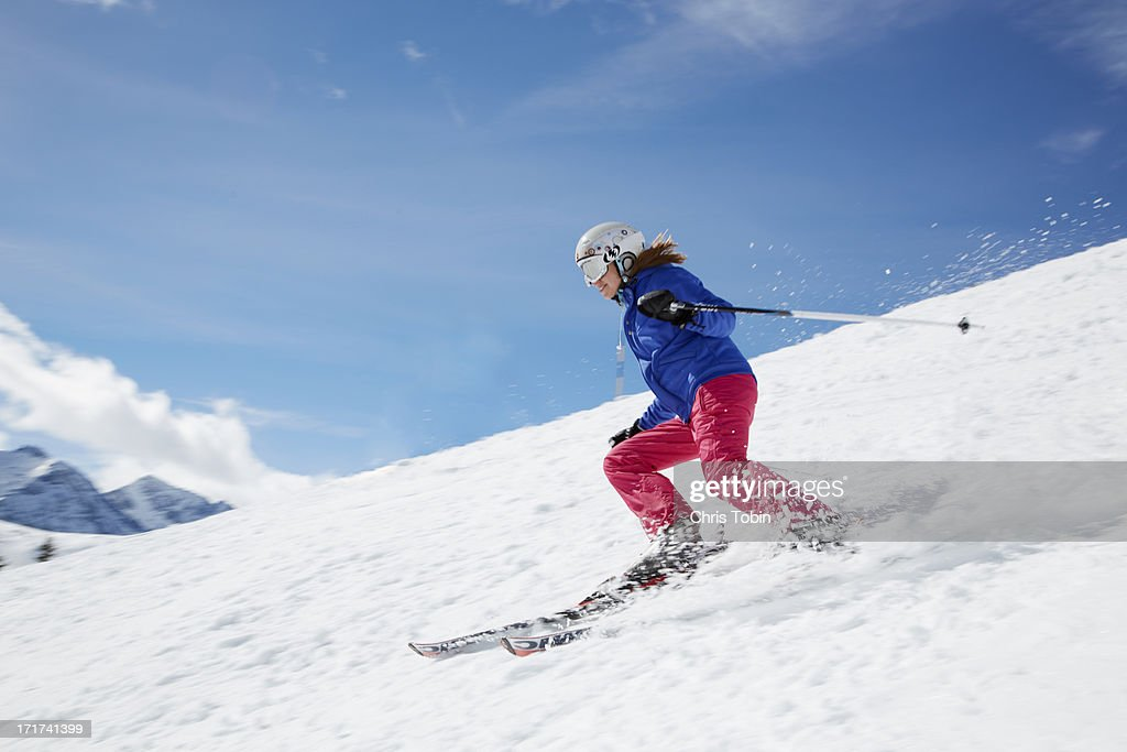 Young woman skiing down mountain : Stock Photo