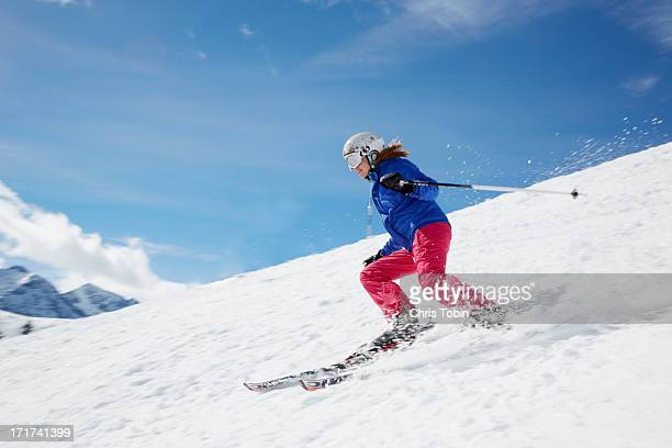 Young woman skiing down mountain