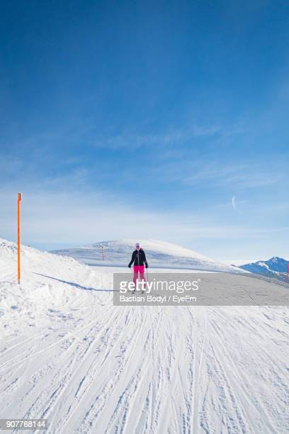 Young Woman Skiing On Slope Against Blue Sky