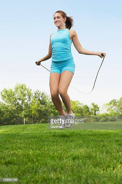 Young woman skipping in garden, smiling