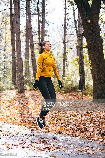 young woman skipping in the park - skipping along stock pictures, royalty-free photos & images