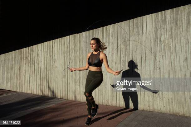 young woman skipping while exercising against wall - skipping along stock pictures, royalty-free photos & images