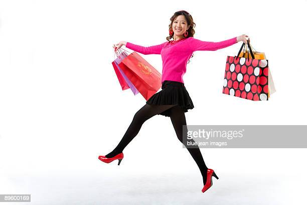 Young woman skipping with her shopping bags