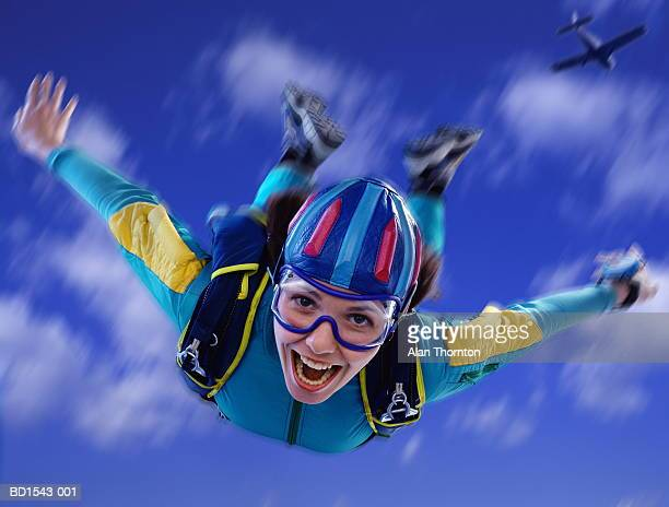 Young woman skydiving, close-up, low angle view (Digital Composite)