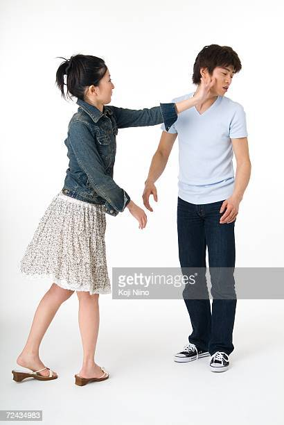 young woman slapping her boyfriend - slapping stock pictures, royalty-free photos & images