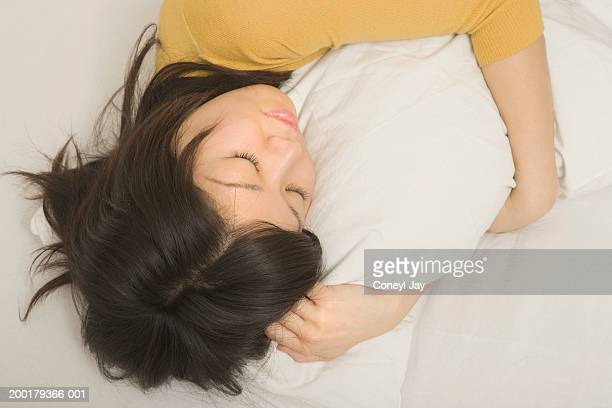 young woman sleeping, hugging pillow, elevated view - coneyl stock pictures, royalty-free photos & images