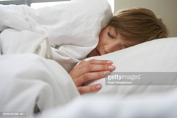 Young woman sleeping in bed, close-up