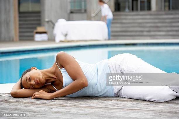 Young woman sleeping near swimming pool, side view