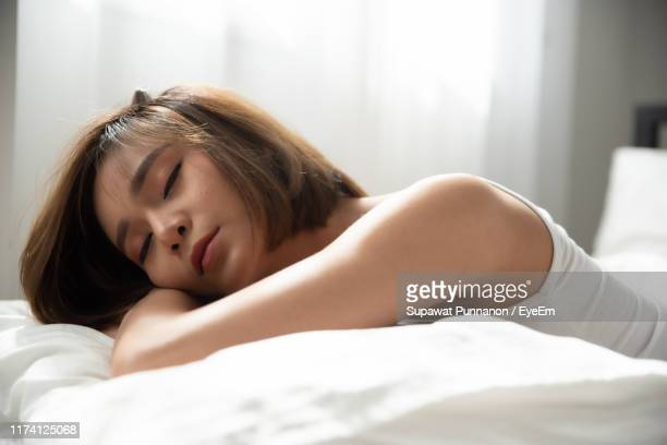young woman sleeping on bed at home - china foto e immagini stock