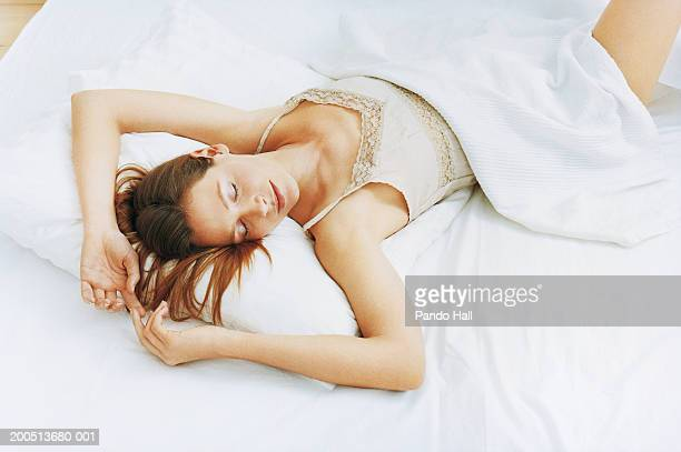 young woman sleeping on bed, elevated view - women in slips stock pictures, royalty-free photos & images
