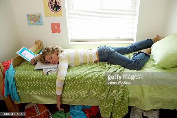 young woman sleeping on bed in student dorm, head resting on books - erin james stock-fotos und bilder