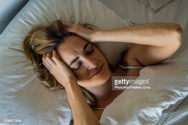 young woman sleeping on bed - problems stock pictures, royalty-free photos & images