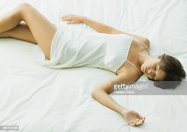 young woman sleeping on bed - women in slips stock pictures, royalty-free photos & images
