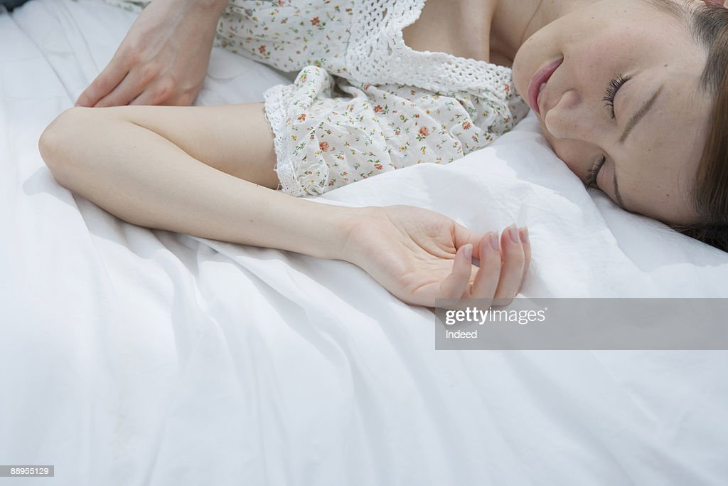 Young woman sleeping on bed : Stock Photo