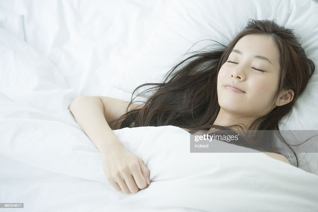 Young woman sleeping on bed, portrait : ストックフォト