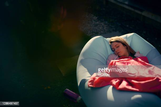 young woman sleeping on inflatable sun lounger - mid adult stock pictures, royalty-free photos & images