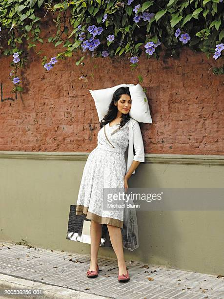 young woman sleeping with pillow against wall - dormir humour photos et images de collection