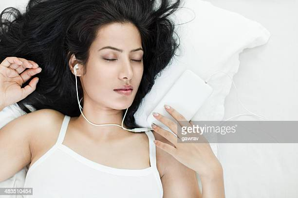 Young woman sleeping with smart phone and headphones on.