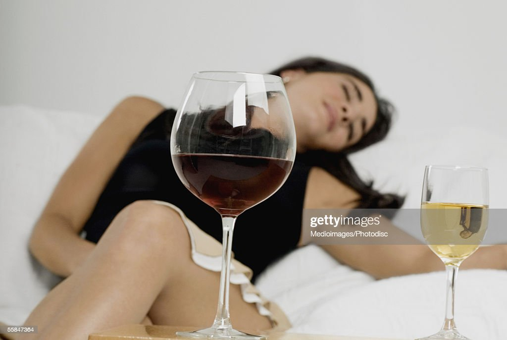Young woman sleeping with wineglasses in front of her : Stock Photo