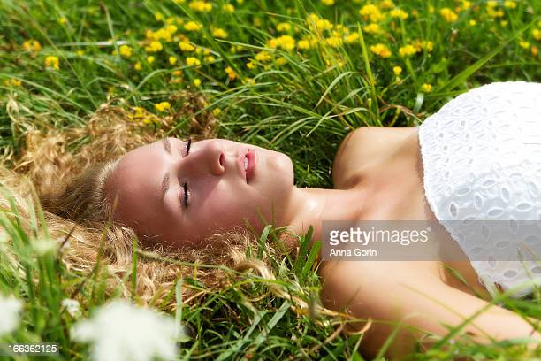 young woman sleeps in field of flowers - state college stock photos and pictures