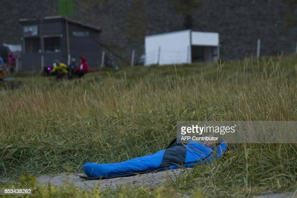A young woman sleeps on the beach during the Lofoten Masters 2017 the world's most northerly surf competition in Unstad's bay in the arctic circle on...