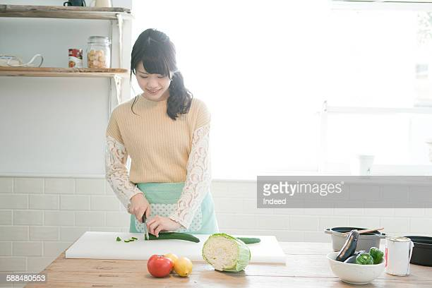 Young woman slicing cucumber at kitchen