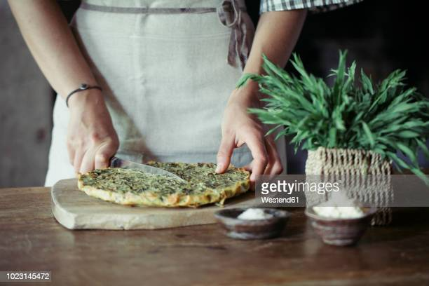 Young woman slicing homemade chickpea and herb cake