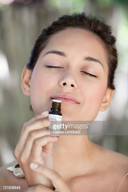 Young woman smelling aromatherapy oil