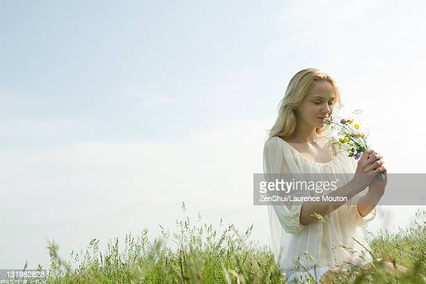 Young woman smelling bouquet of wildflowers