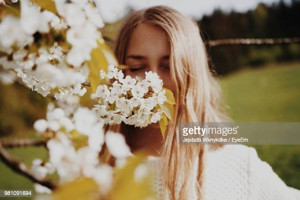 Young Woman Smelling Flowers At Park