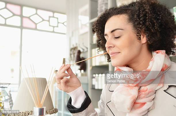 Young woman smelling joss sticks in boutique