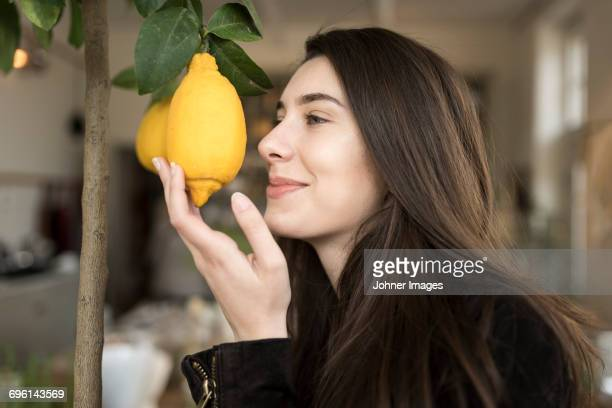 Young woman smelling lemon
