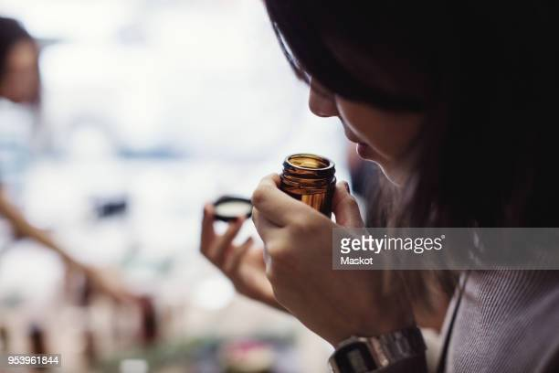 young woman smelling perfume from bottle at workshop - olores agradables fotografías e imágenes de stock