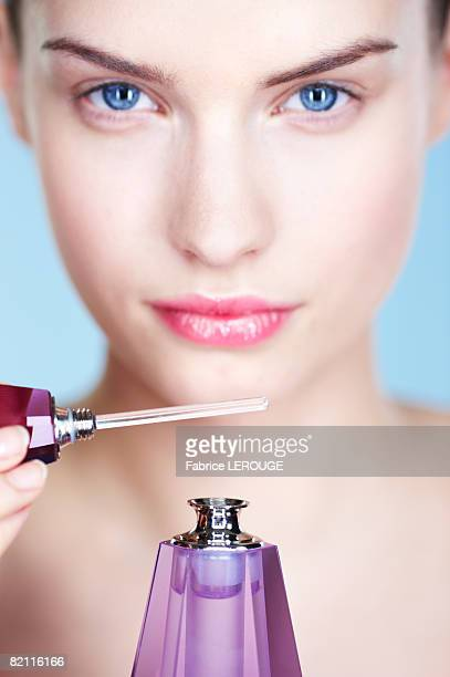 Young woman smelling perfume