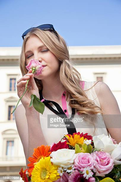 young woman smelling rose from bouquet of flowers, eyes closed - long stem flowers stock pictures, royalty-free photos & images