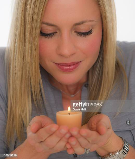 Young woman smelling scented candle