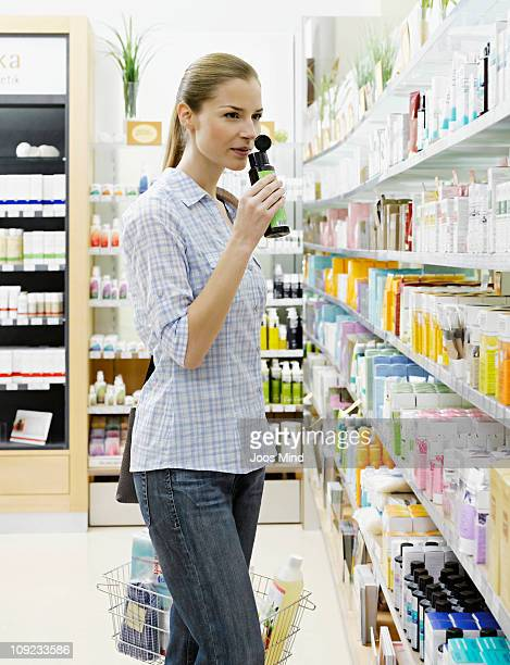 young woman smelling shampoo in chemist shop