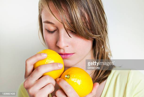 Young woman smelling the scent of lemons, close-up