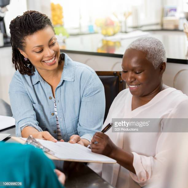 young woman smiles as a senior patient fills out application - form filling stock photos and pictures