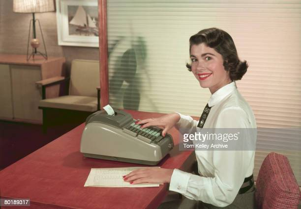 A young woman smiles as she poses at a desk in an officelike environment one hand on a document and the other on the keys of a Clary adding machine...
