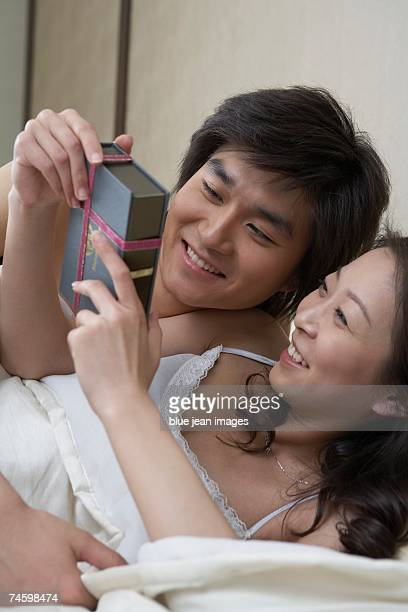 a young woman smiles as she receives a gift from the young man in bed beside her. - nur erwachsene stock-fotos und bilder