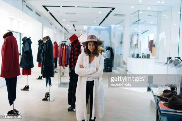 young woman smiles at camera while trying on outfit - long coat stock pictures, royalty-free photos & images