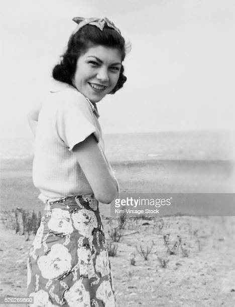 Young woman smiles coyly while at the beach